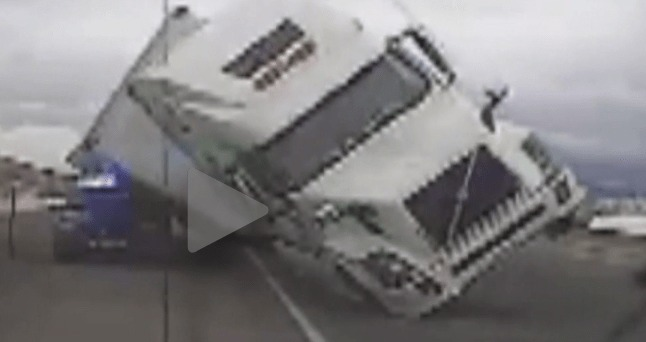 Video Catches Tractor-Trailer Blowing Over Onto Police Unit