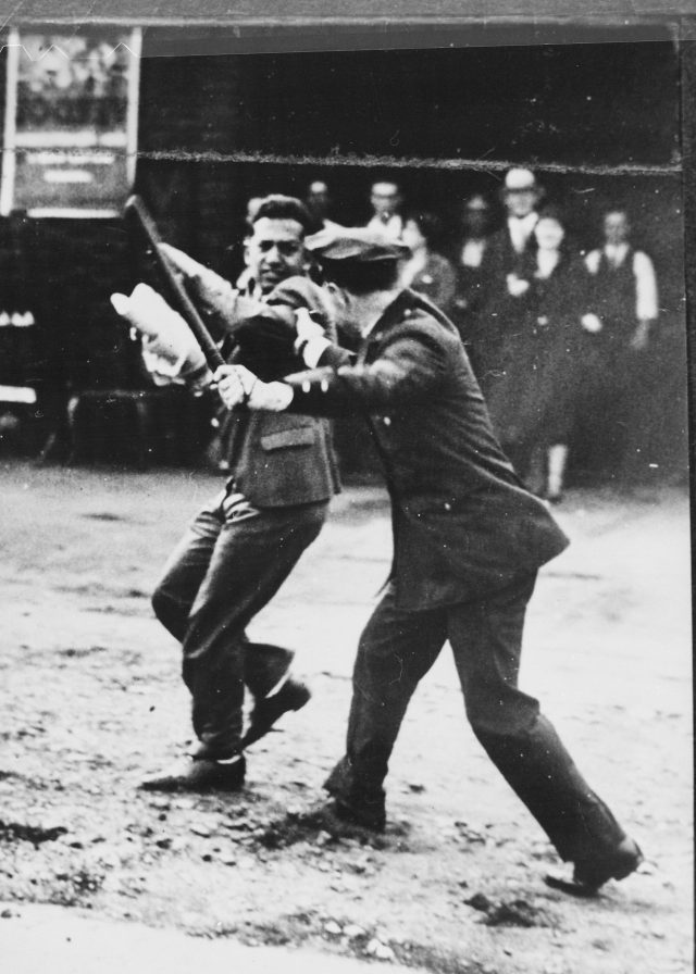 (Police with nightstick. This work is in the public domain courtesy of U.S. National Archives and Records Administration.)