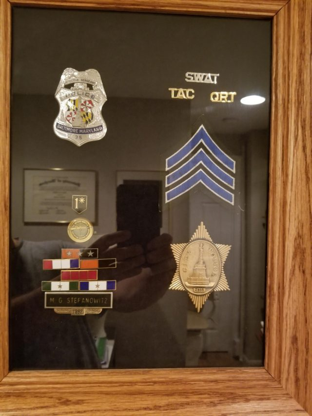 Michael J. Stefanowitz is reflected in a shadow box commemorating his career with the Baltimore police department.