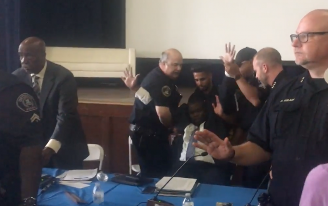 Police commissioner removed from meeting in handcuffs