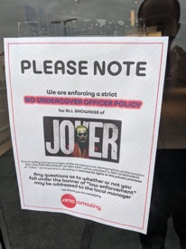 Signs posted at movie theater saying no cops allowed