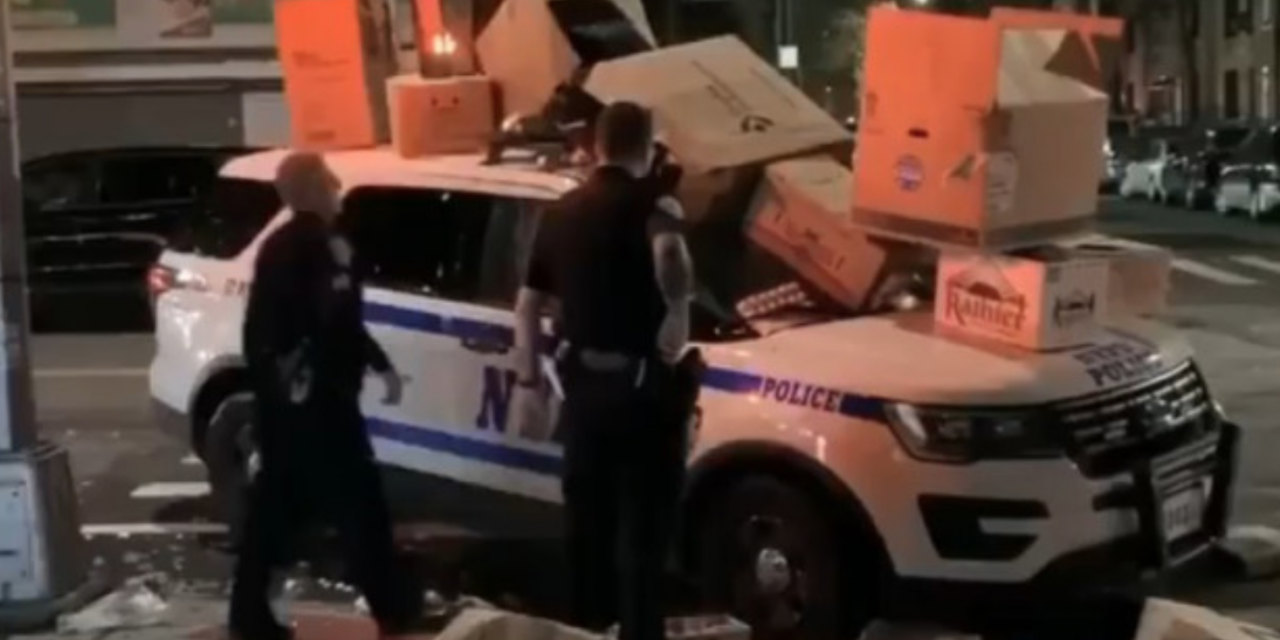 NYPD cruiser covered in burning trash as onlookers laugh