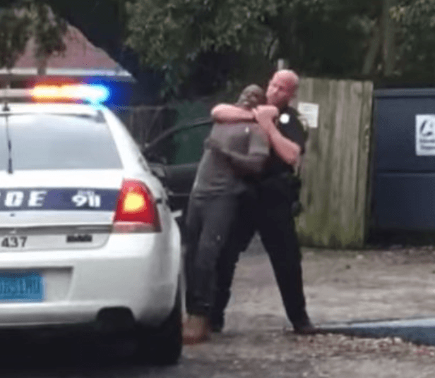 Officer under investigation for placing suspect in a headlock who was spitting in his face