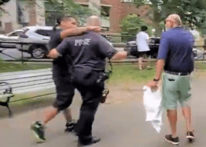 """Ironically, a police officer eventually intervened to protect the Latino assailant from the angry crowd after he assaulted the senior citizen. One man in the crowd yells at the attacker as he cowers behind the police officer: """"Now you want the cops! NOW you want them, huh?"""""""