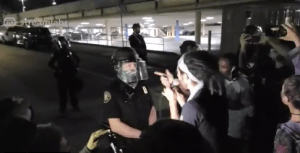 Portland based rapper/protestor calling himself No$hu freestyle challenges a Portland police office in riot gear, on the 101st night of protests in the city.