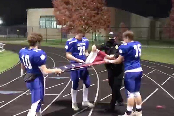 True patriot: Police officer teaches football players how to properly fold the American flag