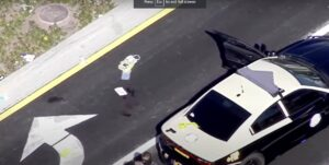 Ariel view of scene shows suspect's gun on police car trunk - Screenshot courtesy of WPLG on YouTube
