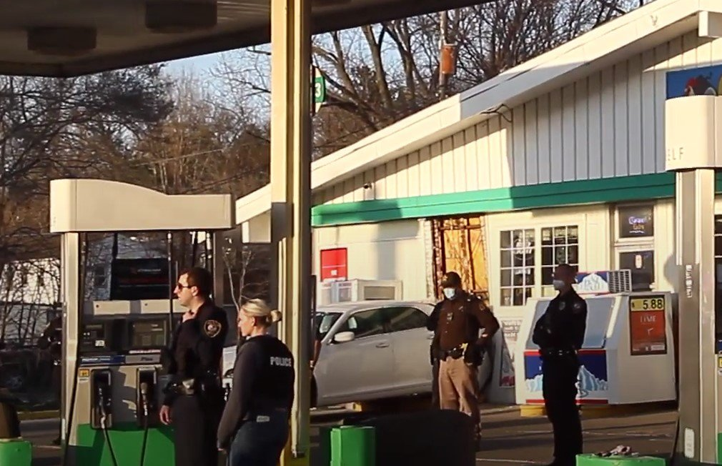 This vehicle backed into the gas station building while dragging officers - Screenshot courtesy of Quad-City Times on YouTube
