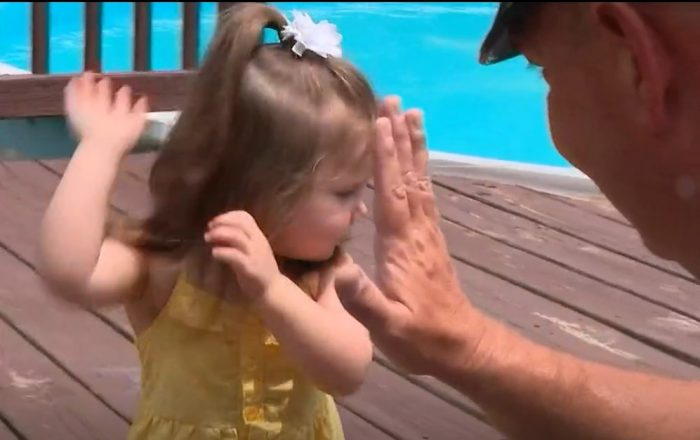 Two-year-old Carmella gives her rescuer a high-five - Screenshot courtesy of WBNS News