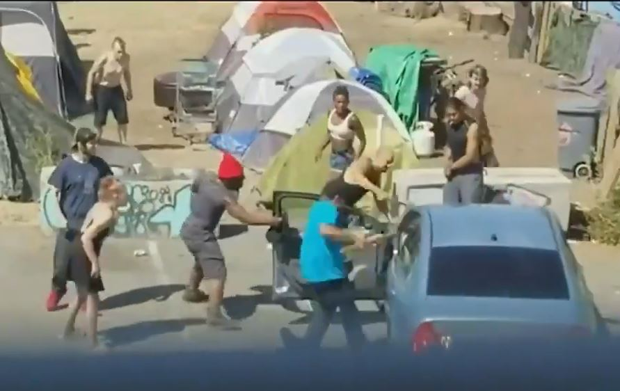 Video: Felons at homeless encampment attack couple with infant in car