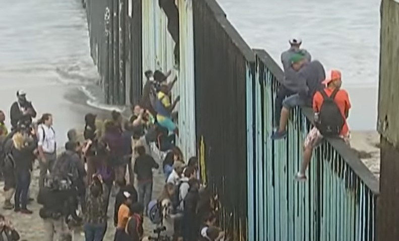 Central American migrants climb over a border wall into the U.S. in 2018 - Screenshot courtesy of CBS News on YouTube